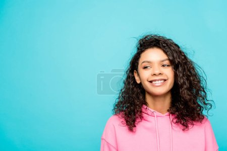 Photo for Cheerful african american girl smiling while standing isolated on blue - Royalty Free Image