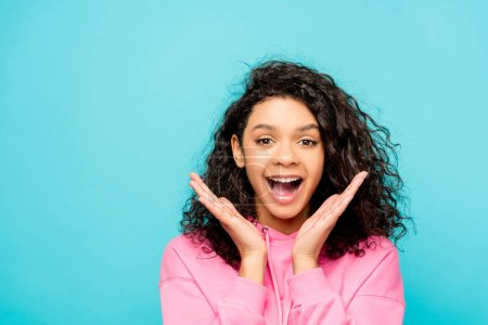 Photo for Excited curly african american girl screaming while standing isolated on blue - Royalty Free Image