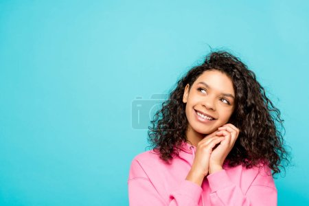 dreamy curly african american girl smiling while standing isolated on blue