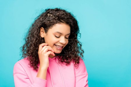 Photo for Happy curly african american girl smiling isolated on blue - Royalty Free Image