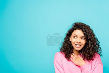 dreamy pretty african american girl smiling isolated on blue