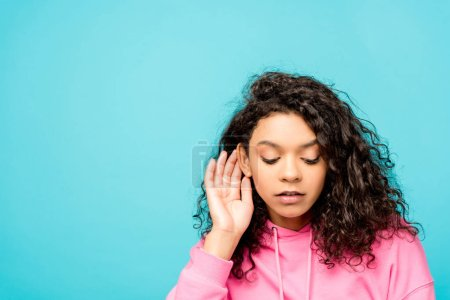 Photo for Beautiful curly african american girl touching ear isolated on blue - Royalty Free Image