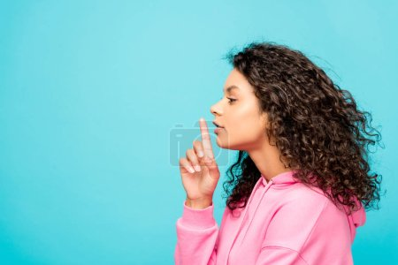 Photo for Side view of curly african american girl showing hush sign isolated on blue - Royalty Free Image