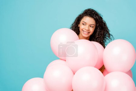Photo for Pretty curly african american girl smiling near pink air balloons isolated on blue - Royalty Free Image