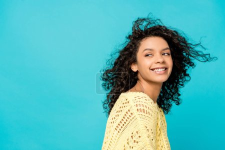 beautiful curly african american woman smiling isolated on blue