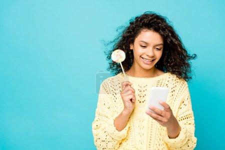feliz rizado afroamericano chica sosteniendo piruleta y el uso de teléfono inteligente aislado en azul