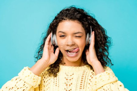 Photo for Attractive curly african american girl listening music in headphones and showing tongue isolated on blue - Royalty Free Image