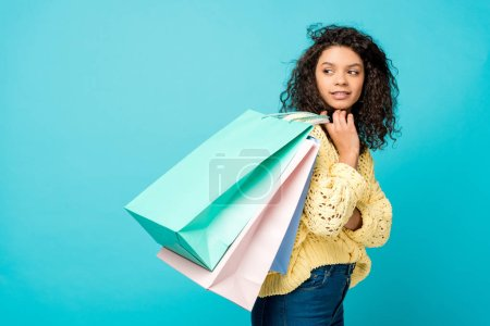 attractive curly african american girl holding shopping bags while standing isolated on blue