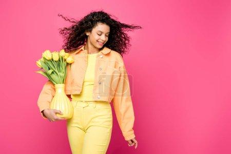 Photo pour Gai afro-américaine fille tenant vase avec des tulipes jaunes tout en se tenant isolé sur cramoisi - image libre de droit