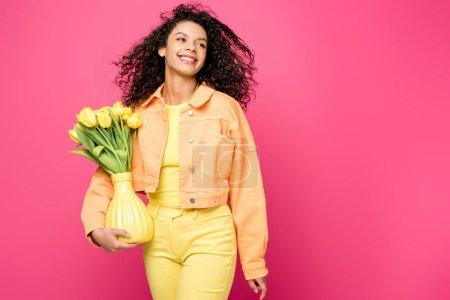 glückliches afrikanisch-amerikanisches Mädchen hält Vase mit gelben Tulpen, während es isoliert auf purpurrotem Grund steht