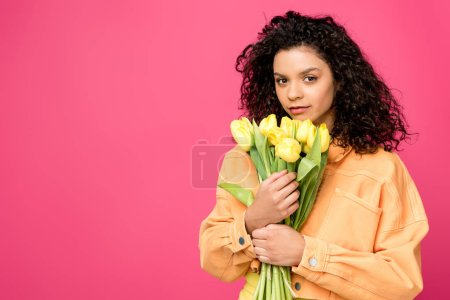 Photo for Attractive curly african american girl holding yellow tulips isolated on crimson - Royalty Free Image