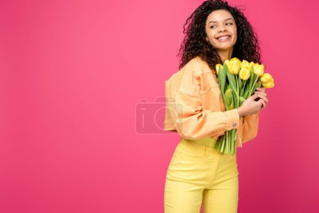 Photo for Beautiful curly african american girl smiling while holding yellow tulips isolated on crimson - Royalty Free Image