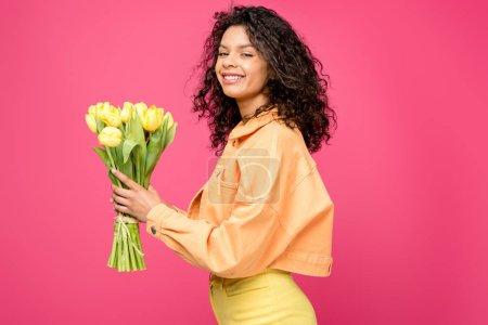 glückliche afrikanisch-amerikanische Frau hält gelbe Tulpen isoliert auf purpurrot