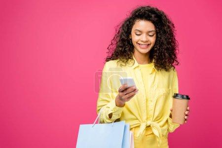 Photo pour Femme afro-américaine bouclée avec des sacs à provisions regardant smartphone tout en tenant tasse en papier isolé sur cramoisi - image libre de droit