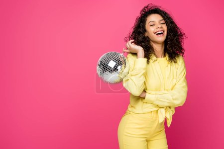 Photo for Happy african american woman holding shiny disco ball isolated on crimson - Royalty Free Image