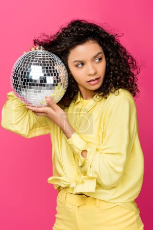 Photo for Attractive african american woman holding shiny disco ball isolated on crimson - Royalty Free Image