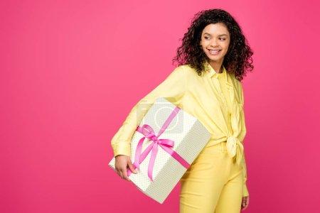 Foto de Alegre mujer afroamericana rizado sosteniendo caja de regalo con cinta de raso rosa aislada en carmesí - Imagen libre de derechos