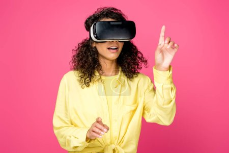 surprised curly african american woman wearing virtual reality headset and pointing with fingers isolated on crimson