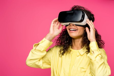 Photo for Cheerful african american woman wearing virtual reality headset isolated on crimson - Royalty Free Image