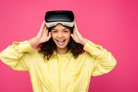 beautiful african american woman wearing virtual reality headset and smiling isolated on crimson