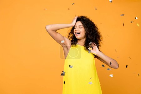 Photo for Cheerful curly african american woman smiling near shiny confetti stars on orange - Royalty Free Image