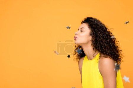 Photo pour Heureux frisé afro-américain fille en robe jaune soufflant près brillant confettis étoiles isolé sur orange - image libre de droit