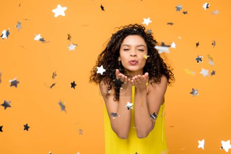 happy curly african american girl in yellow dress sending kiss near shiny confetti stars on orange
