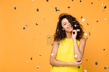 Photo for Happy curly african american girl in yellow dress standing near shiny confetti stars on orange - Royalty Free Image