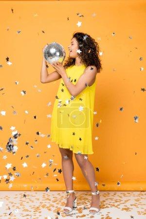 attraktive lockige Afroamerikanerin mit Discokugel in der Nähe glänzender Konfetti-Sterne auf Orange