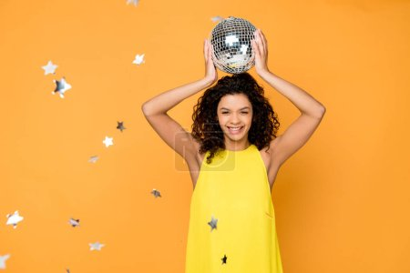 selective focus attractive curly african american girl holding disco ball above head near shiny confetti stars on orange