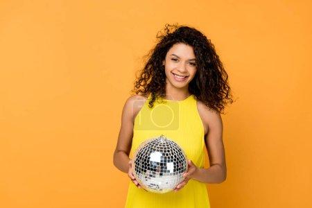 Foto de Chica afroamericana en vestido amarillo sosteniendo bola de discoteca aislada en naranja - Imagen libre de derechos