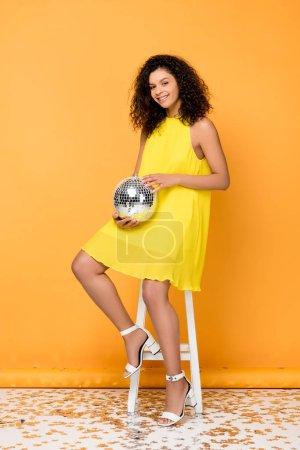 Foto de Alegre mujer afroamericana rizada sosteniendo bola de discoteca mientras está sentada en la silla en naranja - Imagen libre de derechos
