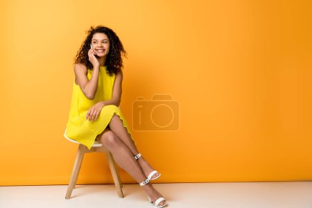 Photo for Happy curly african american woman sitting in yellow dress on chair and talking on smartphone on orange - Royalty Free Image