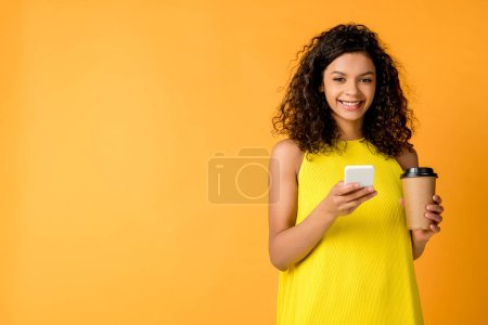 Photo for Cheerful curly african american woman using smartphone while holding paper cup isolated on orange - Royalty Free Image