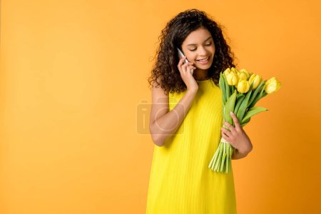 Photo for Happy curly african american girl talking on smartphone while holding yellow tulips isolated on orange - Royalty Free Image