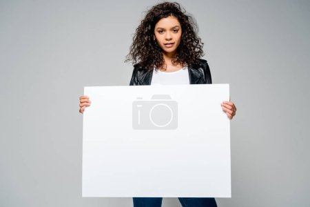 Photo for Beautiful curly african american girl holding blank placard while standing isolated on grey - Royalty Free Image