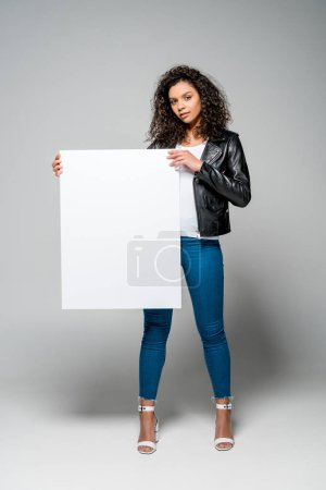 Photo for Beautiful curly african american woman holding blank placard while standing on grey - Royalty Free Image