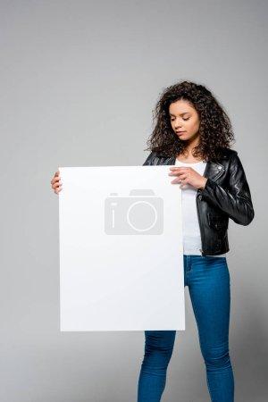 Photo pour Attrayant bouclés femme afro-américaine tenant blanc plaque tout en restant sur le gris - image libre de droit