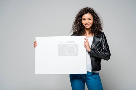 Photo for Cheerful curly african american woman holding blank placard while standing isolated on grey - Royalty Free Image