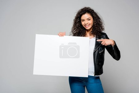 happy african american young woman pointing with finger at blank placard while standing isolated on grey