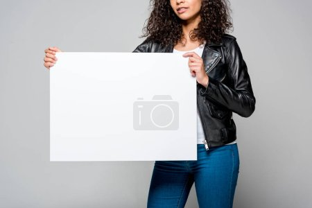 Photo for Cropped view of african american young woman holding blank placard isolated on grey - Royalty Free Image