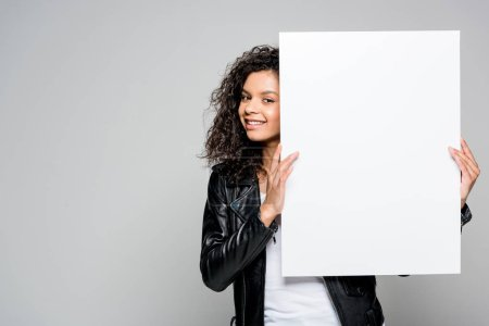 Photo for Smiling pretty african american young woman holding blank placard isolated on grey - Royalty Free Image