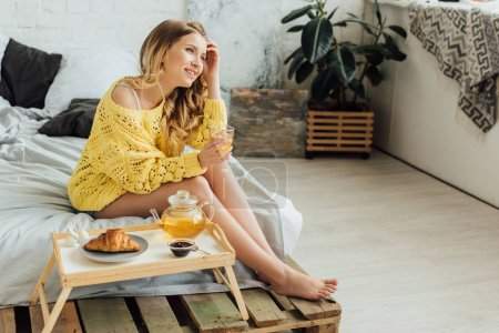 beautiful girl sitting near tray with food and pouring tea in cup during breakfast in bedroom