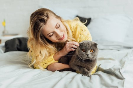 beautiful girl in knitted sweater lying in bed and hugging scottish fold cat