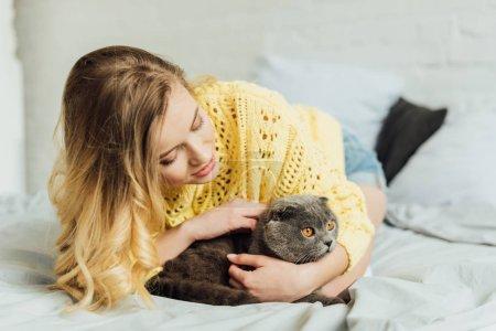 Photo pour Belle fille en tricot pull couché dans le lit et câlin écossais plier chat - image libre de droit