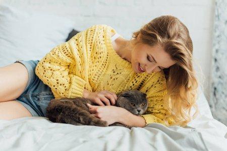 Photo pour Belle fille souriante en pull tricoté couché dans le lit et étreignant le chat écossais pliant - image libre de droit