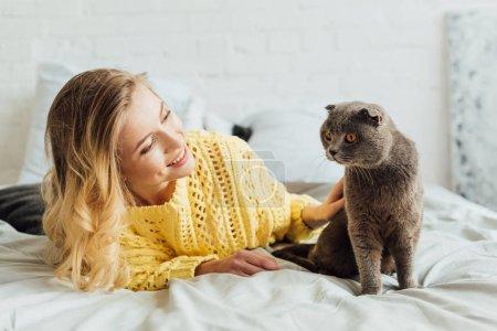 Photo pour Belle fille souriante en tricot pull caressant chat écossais pliant tout couché dans le lit à la maison - image libre de droit