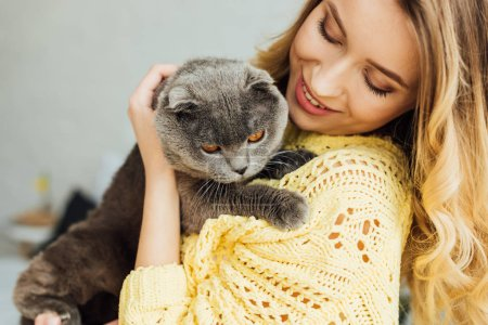 Photo for Selective focus of beautiful smiling girl hugging cute scottish fold cat - Royalty Free Image