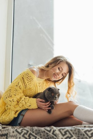 Photo pour Beau sourire jeune femme étreignant le chat écossais de pli tout en s'asseyant sur le rebord de fenêtre avec l'espace de copie - image libre de droit