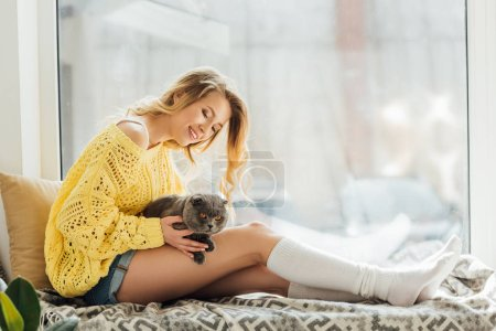 Photo for Beautiful smiling young woman hugging scottish fold cat while sitting on window sill with copy space - Royalty Free Image